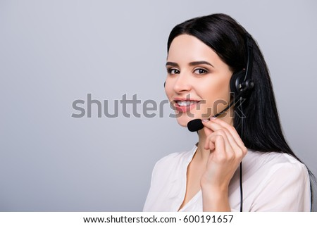 Young consultant in headphones touching microphone and giving advice to a client #600191657