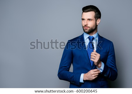 Portrait of serious fashionable handsome man in blue suit and tie  buttoning cufflinks Royalty-Free Stock Photo #600200645