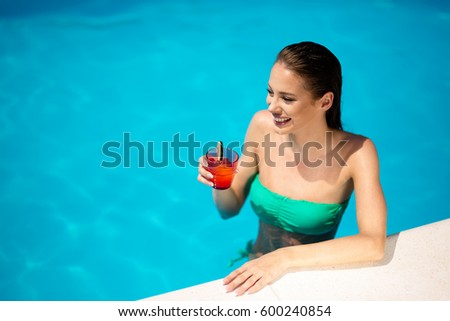 Beautiful woman drinking cocktail and sunbathing at pool #600240854