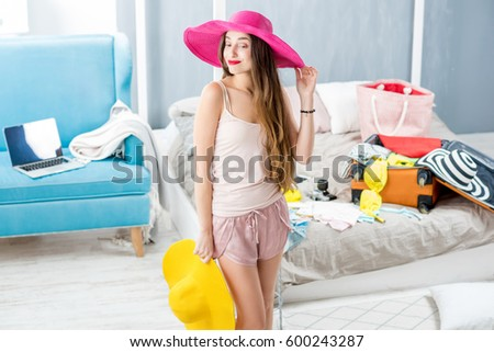 Young woman choosing hat in the bedroom with suitcase and clothes on the background. Prepairing for the summer vacations #600243287