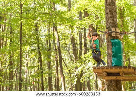 Brave little boy rappelling high among the trees in an Adventure Park for children  #600263153