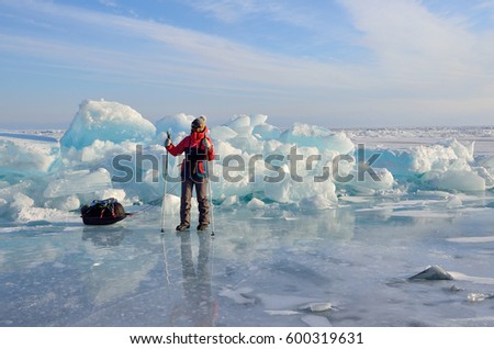 Baikal lake, Russia, March, 01, 2017. Traveler with a sledge-drag going in front of the ice ridges near the village of Bolshie Koty at lake Baikal #600319631