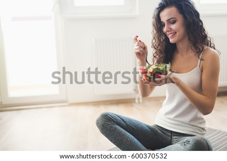 Beautiful fit woman eating healthy salad after fitness workout Royalty-Free Stock Photo #600370532
