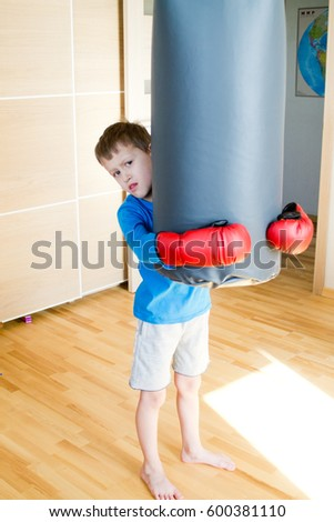 A boy in red boxing gloves  #600381110