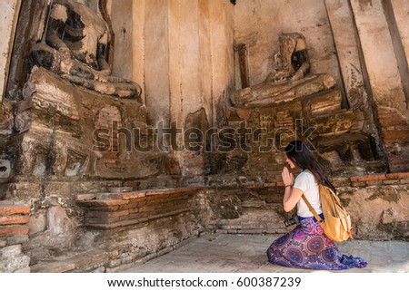 Beautiful asia woman pay respect to buddha statue at Wat Chaiwatthanaram is UNESCO World Heritage, Ayutthaya Historical Park, Thailand. Girl traveler famous tourism attraction during travel vacation. #600387239