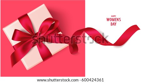 Decorative gift box with red bow and long ribbon. Happy Women's Day text. Top view Royalty-Free Stock Photo #600424361