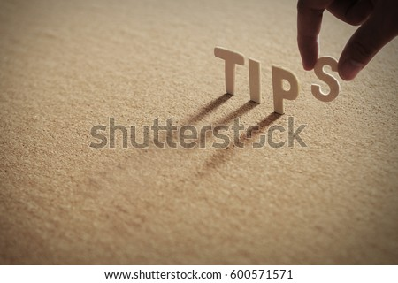 TIPS wood word on compressed or corkboard with human's finger at S letter.