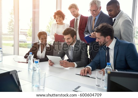 Young business group carefully studying something on tablet in office