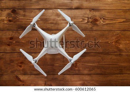 Drone quadcopter on the old wooden background with a copy space. Top view, flat lay composition. #600612065