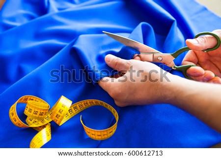 Tailor. Man Hands notch tailor tailor's scissors cloth. Close Up. #600612713