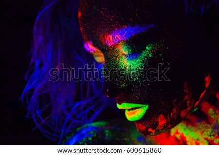 Beautiful extraterrestrial model woman with blue heair and green lips in neon light. It is portrait of beautiful model with fluorescent make-up, Art design of female posing in UV with colorful make up #600615860