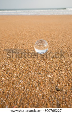 Transparent crystal ball lying on the sand on the beach against the sea m waves. #600765227