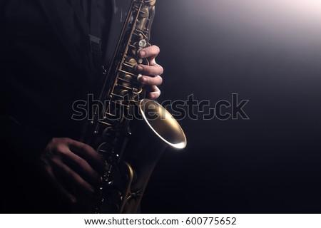 Saxophone player Saxophonist playing jazz music instrument Jazz musician playing sax alto Royalty-Free Stock Photo #600775652
