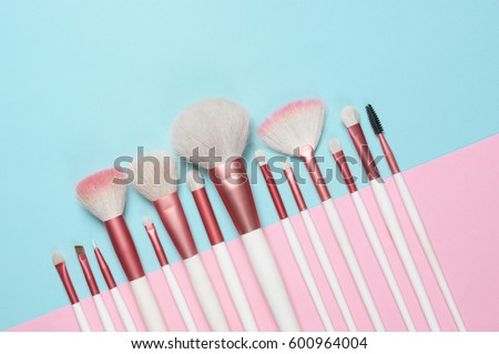 Set of makeup brushes on pink and aqua colored composed background. Top view point, flat lay. Royalty-Free Stock Photo #600964004