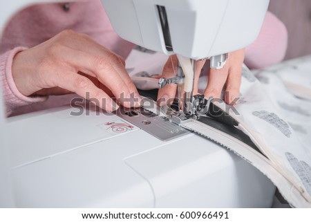 beautiful woman seamstress sew on the sewing machine clothes. sewing workshop #600966491