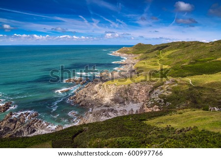 Picturesque view of the North coast of Devon. Grunta beach and Mortehoe point in the distance. Striped sky. England Royalty-Free Stock Photo #600997766