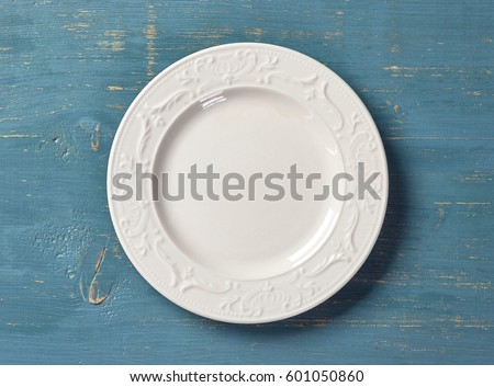 white empty plate on blue wooden table, top view Royalty-Free Stock Photo #601050860