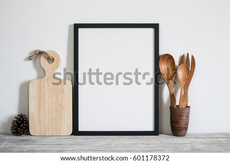 mock up frame with utensils on wooden table in kitchen room