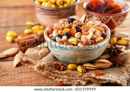 Mix of nuts and dried fruits on a old rustic table. Gold pistachios, cashews, hazelnuts, almonds. Food background. #601199999