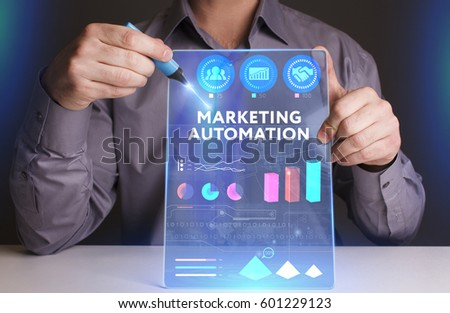 Business, Technology, Internet and network concept. Young businessman working on a virtual screen of the future and sees the inscription: Marketing automation #601229123