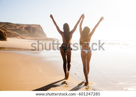 Beautiful girls in bikin walking on the beach