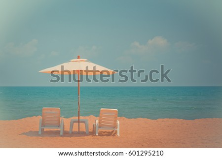 Two beach chairs and white umbrella on the tropical beach at daytime. Vintage tone #601295210
