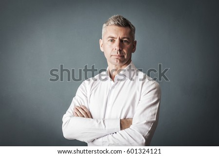 Businessman in white shirt looks at us on gray wall background  #601324121