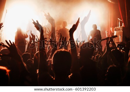 silhouettes of people at a rock festival concert in front of the scene in bright light. Double exposure #601392203