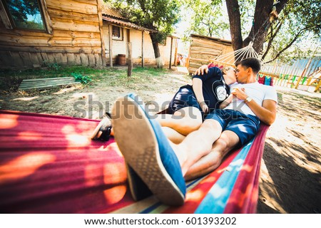 Pregnant woman and her husband, resting in a hammock in the country #601393202
