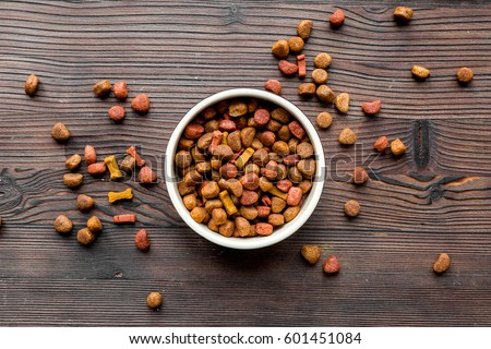 dry dog food in bowl on wooden background top view #601451084