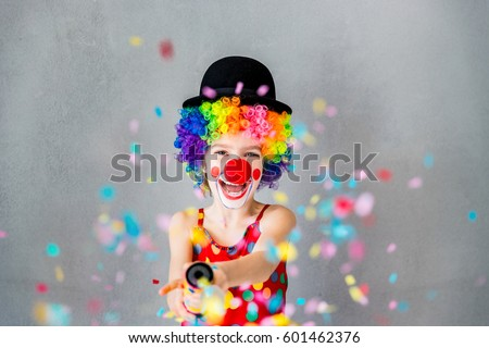 Let's party!! Funny kid clown playing at home. Child shooting party popper confetti. 1 April Fool's day concept #601462376