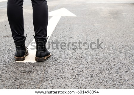 boots on a tarmac road with white direction arrow, the concept of moving forward #601498394