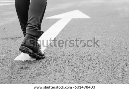boots on a tarmac road with white direction arrow, the concept of moving forward #601498403