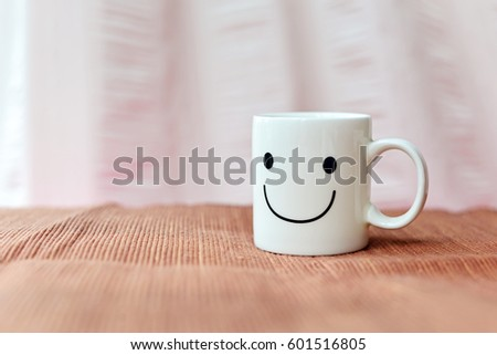 Happy cup on the tablecloth. Concept about happiness and waiting for someone. #601516805