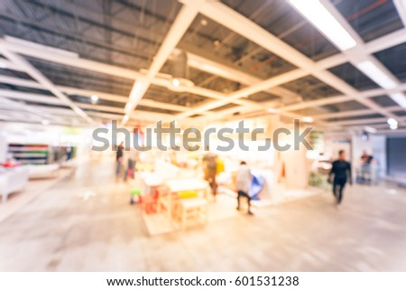 Blurred image vivid kid playing room, play corner in furniture store. Colorful play tunnel, eco-friendly wooden tables, and circus tent with flag on top striped. Active children running. Vintage tone #601531238