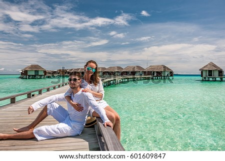 Couple in white on a tropical beach jetty at Maldives #601609847