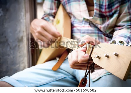 Handsome hands of man playing music with balalaika at grey wall background. Lifestyle concept. Jam session. Russian instrument. #601690682