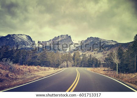 Asphalt road in autumn with moody sky, color toned picture, Colorado, USA. #601713317