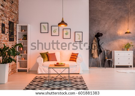 Spacious living room with brick wall, couch, table and lamp #601881383