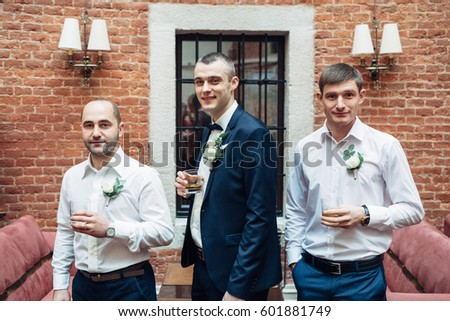 Profile of groom and groomsmen drinking whisky in brick hall #601881749