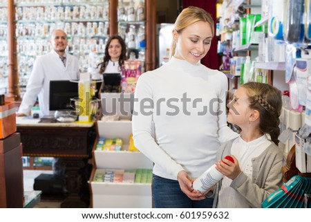 Young mother with a girl consulting two pharmacists at a cash desk in the pharmaceutical store  #601959632