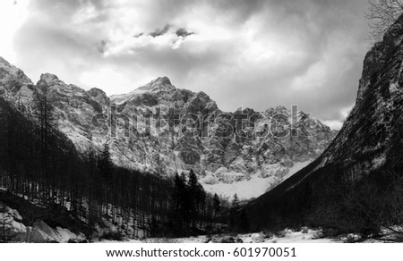 """Vintage black and white mountain landscape (European Alps region).  In the picture is """"The Triglav north wall"""" or just """"The Wall"""", 4 km wide and 1 km high wall over the Vrata valley."""