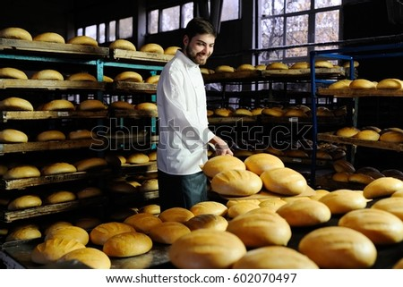 young cute baker smiling pulls out of the oven fresh bread shovel bread #602070497