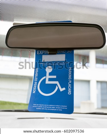 Handicapped placard hanging from car's rear view mirror.