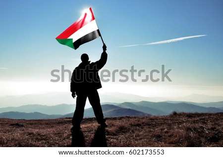 Successful silhouette man winner waving Sudan flag on top of the mountain peak #602173553
