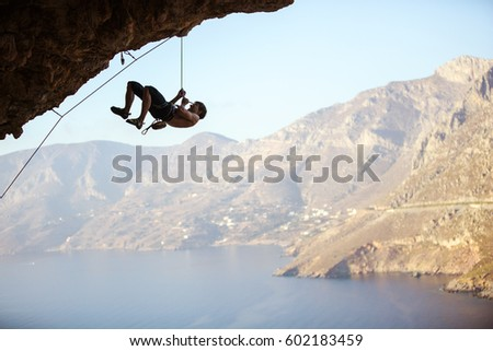 Young man trying to reach cliff in order to continue climbing challenging route. Rock climber pulling himself up and creating rope slack so that belayer could pull in excess rope. #602183459