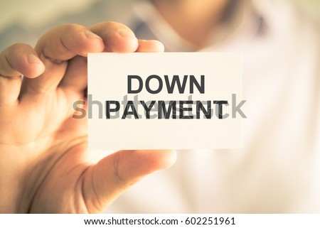 Closeup on businessman holding a card with text DOWN PAYMENT, business concept image with soft focus background and vintage tone #602251961