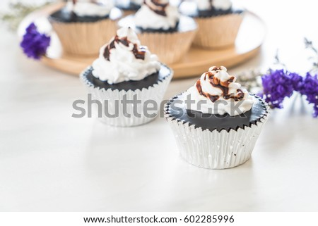 chocolate cup cake with whipped cream on table #602285996