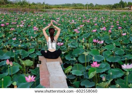 Attractive young woman doing a yoga pose for balance on bridge #602558060
