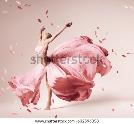 ballerina dancing in flowing pink dress with flying petals in studio #602596358